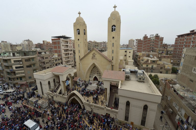 A general view shows people gathering outside the Mar Girgis Coptic Church in the Nile Delta City of Tanta, 120 kilometers (75 miles) north of Cairo, after a bomb blast struck worshippers gathering to celebrate Palm Sunday, April 9, 2017. (AFP/KHALED DESOUKI)