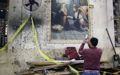 An Egyptian uses his cell phone to take pictures of the destruction, debris, and bloodstains on the walls and icon murals inside the Mar Girgis Coptic Orthodox Church in the Nile Delta City of Tanta on April 9, 2017. (AFP Photo/Stringer)