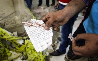 An Egyptian holds out torn a page from a prayer book showing a section of the Gospel of John in Arabic inside the Mar Girgis Coptic Orthodox Church in the Nile Delta City of Tanta, 120 kilometers (75 miles) north of Cairo, at which a bomb blast struck worshippers gathering to attend the Palm Sunday mass, on April 9, 2017. (AFP PHOTO / STRINGER)