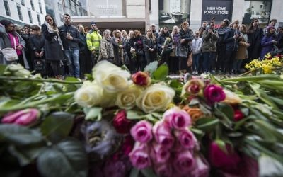 People react during a minute of silence to commemorate the victims of Friday's terror attack at a makeshift memorial near the site where a truck drove into Ahlens department store in Stockholm, Sweden, on April 10, 2017. ( AFP PHOTO / Jonathan NACKSTRAND)