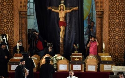 Coptic priests stand near the coffins of victims of the blast at the Coptic Christian Saint Mark's church in Alexandria the previous day during a funeral procession at the Monastery of Marmina in the city of Borg El-Arab, east of the northern port city on April 10, 2017. (AFP Photo/Mohamed El-Shahed)