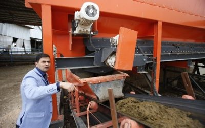 Palestinian engineer Maher Magalsay, who specializes in renewable energy at the Polytechnic University of Hebron, stands by a machine sorting cow dung at the Jebrini dairy farm in the West Bank town of Hebron, where manure is used to produce electricity as an alternative power source, April 10, 2017. (AFP Photo/Hazem Bader)