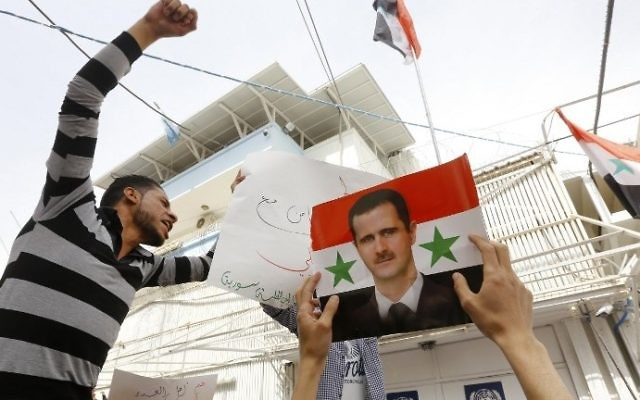 Syrian protesters take part in a demonstration outside the United Nations office in the capital Damascus, on April 11, 2017, in support of the country's strongman Bashar Assad, depicted in the portrait. (AFP Photo/Louai Beshara)