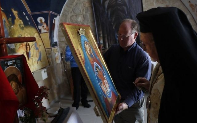 Archbishop Joseph Jules Zerey (R) of the Melkite Greek Catholic Church blesses foreign students of the Bethlehem Icon Center as they present the works executed during their course, in the biblical West Bank city of Bethlehem on April 11, 2017. (AFP PHOTO / THOMAS COEX)