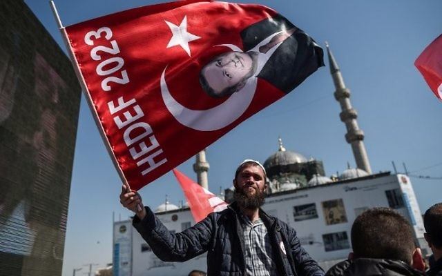 "A man waves a flag with a portrait of Turkish President Recep Tayyip Erdogan on April 11, 2017 during a ""yes"" campaign event in Istanbul's Eminonu district. (AFP PHOTO / OZAN KOSE)"