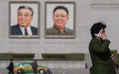 In a photo taken on April 9, 2017 a woman uses a mobile phone as a taxi passes the portraits of late North Korean leaders Kim Il-Sung (L) and Kim Jong-il (R) in Pyongyang. AFP/Ed JONES)