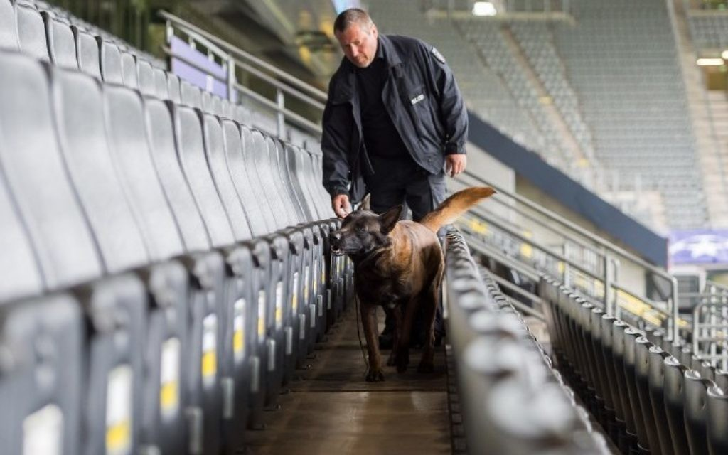 A policeman and an explosive detection sniffer dog do their work at the stadium in Dortmund, western Germany, on April 12, 2017 prior to the UEFA Champions League quarter-final, first-leg football match of German first division Bundesliga club Borussia Dortmund vs Monaco. (AFP PHOTO / DPA / Guido Kirchner)