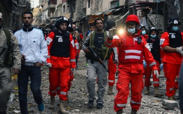 Paramedics walk amid the destruction after clashes that took place earlier in the week between an extremist group and a Palestinian security force, in Ain al-Hilweh refugee camp, near the southern coastal city of Sidon, April 12, 2017. (AFP/STRINGER)