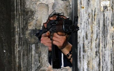 A member of the joint Palestinian security forces takes position through a hole in a wall with a Kalashnikov rifle in the Ain al-Hilweh refugee camp near Sidon, Lebanon, April 12, 2017. (AFP/stringer)
