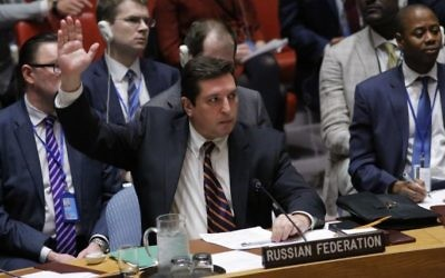 Russian Deputy Permanent Representative to the United Nations Vladimir Safronkov holds up his hand as he votes against a draft resolution that condemned the reported use of chemical weapons in Syria during a meeting at the UN Headquarters in New York, April 12, 2017. (AFP/KENA BETANCUR)