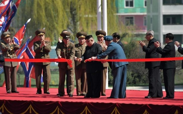 North Korea's leader Kim Jong-Un, center, cuts the red ribbon at a ceremony for the opening of a housing project in Pyongyang on April 13, 2017. (AFP/Ed JONES)