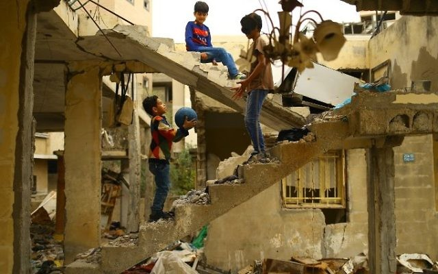 Palestinian children play amidst the ruins of a building destroyed during the 50-day war between Israel and Hamas militants during the summer of 2014 in Gaza City, on April 13, 2017. (Mohammed Abed/AFP)
