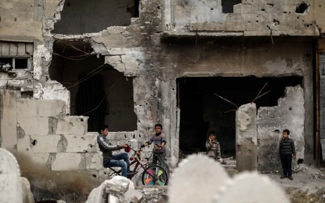 Syrian boys ride bikes amid destroyed buildings in the rebel-held town of Douma, on the eastern outskirts of the Syrian capital Damascus, on April 13, 2017. (AFP/Sameer Al-Doumy)