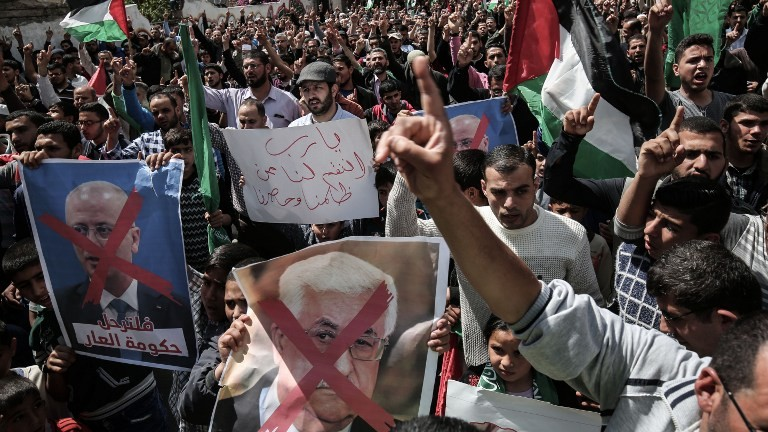 Gaza supporters of the Palestinian Hamas movement hold crossed-out portraits of Palestinian leader Mahmud Abbas (C) and prime minister Rami Hamdallah during a protest on April 14, 2017, in Khan Yunis. (AFP PHOTO / SAID KHATIB)