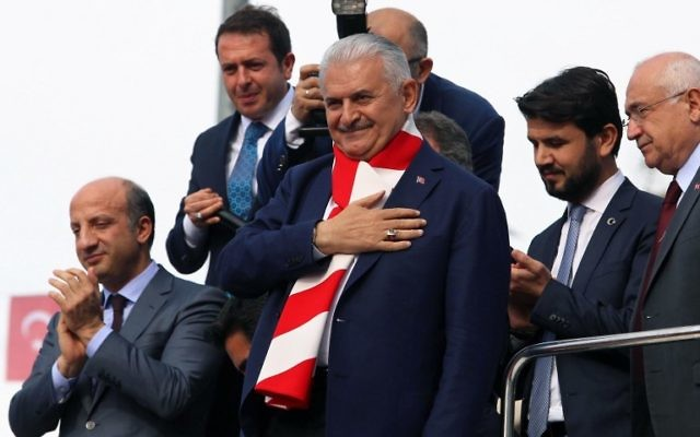 """Turkish Prime Minister and head of Turkey's ruling Justice and Development Party (AKP) Binali Yildirim, center, gestures to a crowd in the Etimesgut district of Ankara, during a """"yes"""" campaign rally ahead of a constitutional referendum on expanding the president's powers, April 14, 2017. (AFP/ADEM ALTAN"""