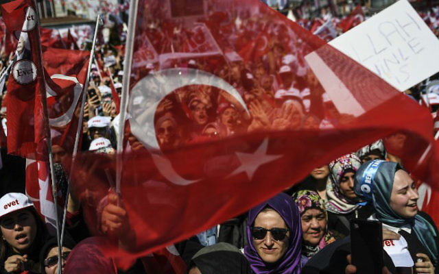 People cheer and wave the national flag as Turkey's president delivers a speech during a rally on the eve of the constitutional referendum, on April 15, 2017 in Istanbul. (Bulent Kilic/AFP)