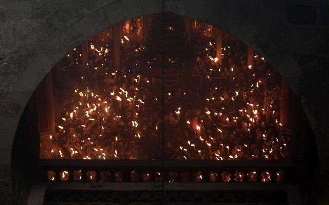 """Christian Orthodox worshipers hold up candles during the ceremony of the """"Holy Fire"""" as thousands gather in the Church of the Holy Sepulchre in Jerusalem's Old City, on April 15, 2017, during the Orthodox Easter holy week. (AFP PHOTO / MENAHEM KAHANA)"""