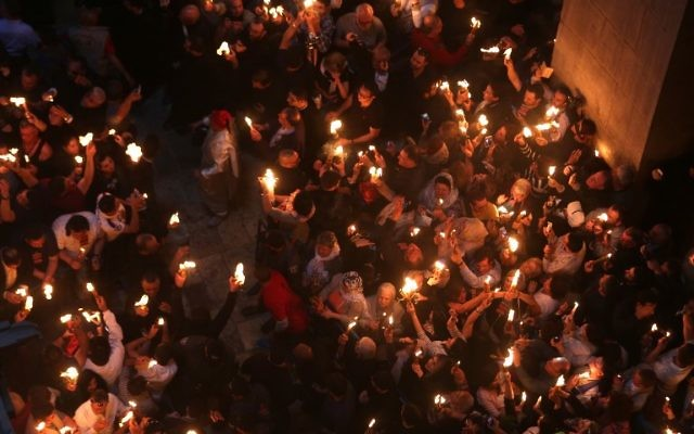 """Christian Orthodox worshipers hold up candles during the ceremony of the """"Holy Fire"""" as thousands gather in the Church of the Holy Sepulchre in Jerusalem's Old City, on April 15, 2017, during the Orthodox Easter holy week. ( AFP PHOTO / MENAHEM KAHANA)"""