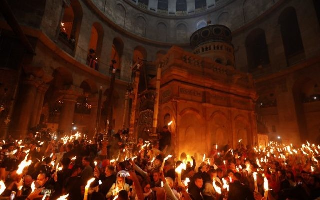 """Christian Orthodox worshipers hold up candles during the ceremony of the """"Holy Fire"""" as thousands gather in the Church of the Holy Sepulchre in Jerusalem's Old City, on April 15, 2017, during Orthodox Easter ceremonies (AFP PHOTO / GALI TIBBON)"""