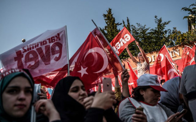 """People cheer and wave Turkish national flags or flags reading """"yes"""" while the Turkish president delivers a speech in Istanbul, on April 15, 2017, during a rally on the eve of the constitutional referendum. (Ozan Kose/AFP)"""
