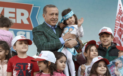Turkish President Recep Tayyip Erdogan poses with children after a rally on April 15, 2017, in Istanbul on the eve of the constitutional referendum. (Ozan Kose/AFP)