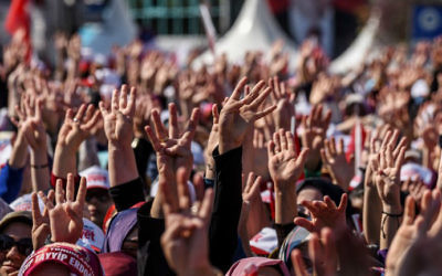 "People cheer and flash a four-finger sign called ""the rabia sign"" as the Turkish president delivers a speech in Istanbul, on April 15, 2017, during a rally on the eve of the constitutional referendum. (Ozan Kose/AFP)"