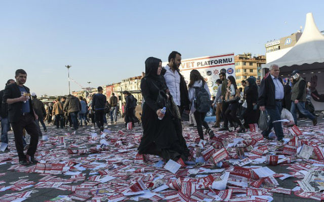 "A couple walk on leaflets reading ""yes"" thrown on the ground at the Kadikoy district, in Istanbul, on the eve of the constitutional referendum, on April 15, 2017. (Bulent Kilic/AFP)"