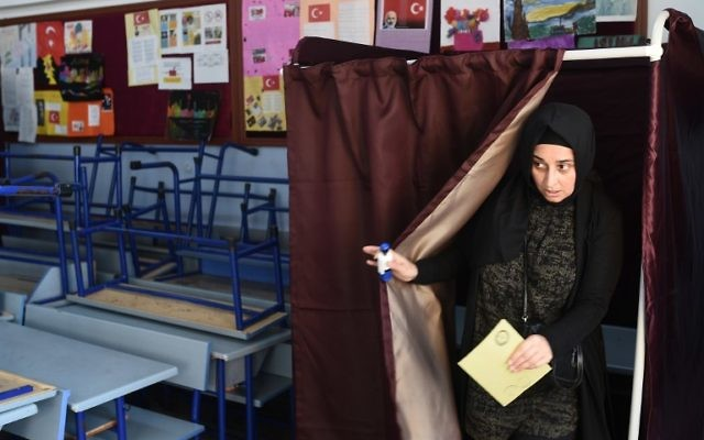 A woman holds her ballot as she readies to vote in the referendum on expanding the powers of the Turkish president, in Istanbul, April 16, 2017. (AFP/OZAN KOSE)