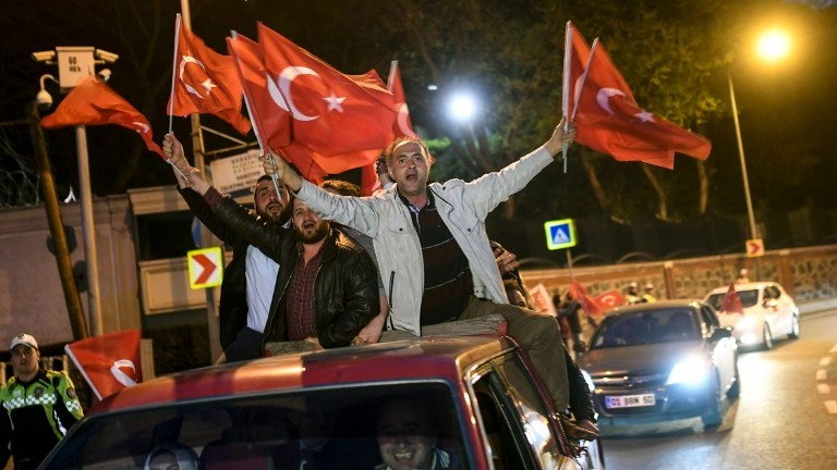 "Supporters of the ""yes"" side wave Turkish flags as they sit on the roof of a car by the presidential residence in Istanbul's Sariyer district on April 16, 2017. (AFP Photo/Bulent Kilic)"
