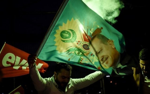 "A supporter of the ""yes"" side waves a flag depicting Turkish President Recep Tayyip Erdogan during a rally near the headquarters of the conservative Justice and Development Party (AKP) on April 16, 2017 in Istanbul. (AFP Photo/Ozan Kose)"