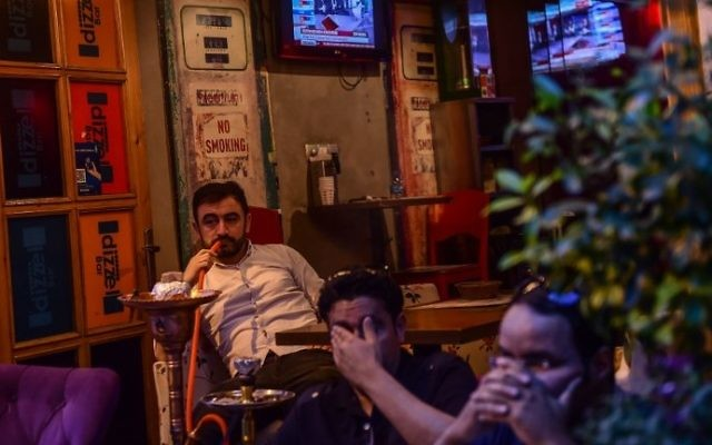 A man smokes a water pipe as others follow the referendum results on television near Taksim square in Istanbul on April 16, 2017. (AFP Photo/Yasin Akgul)