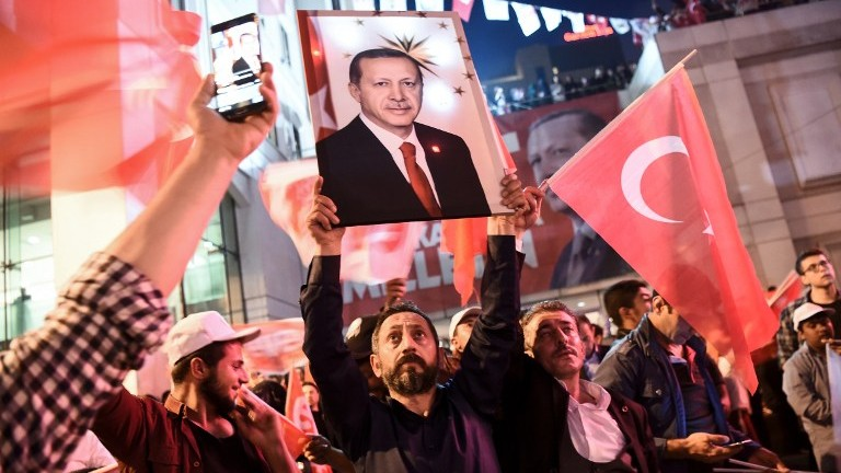 A supporter of the 'Yes' side brandishes a picture of Turkish President Recep Tayyip during a rally near the headquarters of the conservative Justice and Development Party (AKP) on April 16, 2017 in Istanbul. (AFP Photo/Ozan Kose)