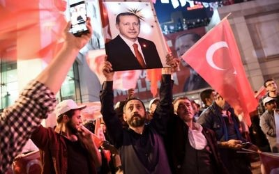 A supporter of the 'Yes' campaign brandishes a picture of Turkish president Recep Tayyip Erdogan among other supporters waving Turkish national flags at a rally near the headquarters of the conservative Justice and Development Party (AKP) on April 16, 2017 in Istanbul after the initial results of a nationwide referendum that will determine Turkey's future destiny. (AFP/Ozan Kose)
