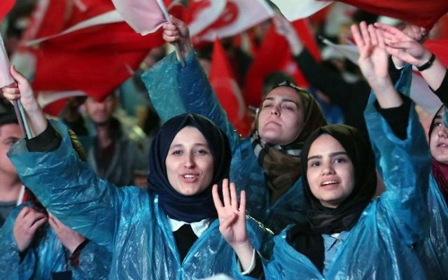 "Supporters of Turkey's president flash a four fingers sign called ""the rabia sign"" as they wave Turkish flags and flags reading ""yes"" during a rally near the headquarters of the conservative Justice and Development Party (AKP) on April 16, 2017 in Ankara. (AFP Photo/Adem Altan)"