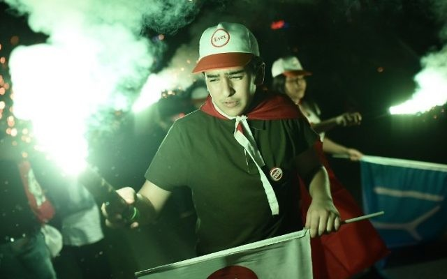 "A supporter of Turkey's president wearing a cap reading ""yes"" holds a smoke bombs during a rally near the headquarters of the conservative Justice and Development Party (AKP) on April 16, 2017 in Istanbul. (AFP Photo/Ozan Kose)"