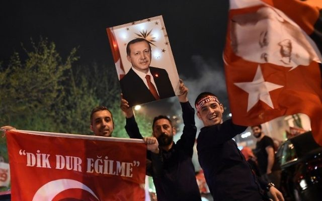"A supporter of the ""yes"" side brandishes a picture of Turkish President Recep Tayyip Erdogan during a rally near the headquarters of the conservative Justice and Development Party (AKP) on April 16, 2017 in Istanbul. (AFP Photo/Ozan Kose)"