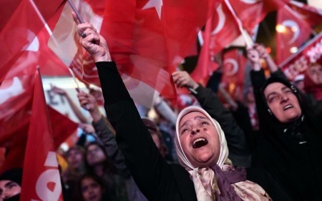 A woman supporting Turkish president waves a Turkish national flag as she celebrates during a rally near the headquarters of the conservative Justice and Development Party (AKP) on April 16, 2017 in Istanbul after the results of a nationwide referendum that will determine Turkey's future destiny. (AFP/Ozan Kose)