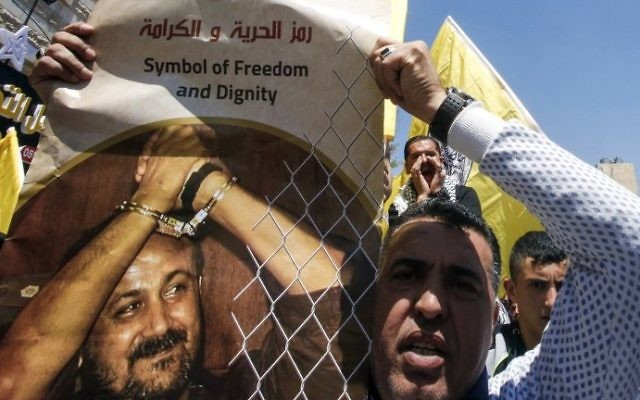 A man holds a photo of Marwan Barghouti calling for his release during a rally supporting Palestinian prisoners detained in Israeli jails in the West Bank city of Hebron on April 17, 2017. (AFP PHOTO / HAZEM BADER)