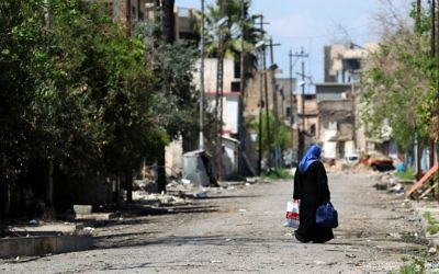 A displaced Iraqi woman from the old city of Mosul walks down a street on April 17, 2017, during an offensive by Iraqi security forces to recapture the city from Islamic State group fighters. (AFP/Ahmad Al-Rubaye)