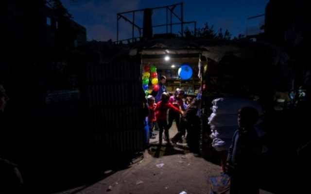 Palestinian children stand at the entrance of a shop lit up using a generator during a power cut in a poor neighborhood of Beit Lahiya, in the northern Gaza Strip, April 17, 2017. (AFP/MAHMUD HAMS)