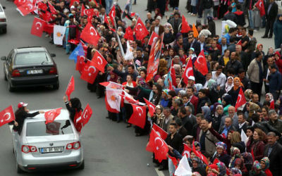 Supporters of Turkish President Recep Tayyip Erdogan cheer and wave Turkish national flags as the presidential convoy parades in Ankara, on April 17, 2017 following the results of a nationwide referendum on Erdogan's powers. (Adem Altan/AFP)