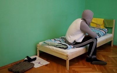 A Chechen gay man who fled persecution in his home Russia's Muslim region of Chechnya due to his sexual orientation, sits on his bed in Moscow on April 17, 2017. (AFP/Naira Davlashyan)
