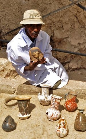 A member of an Egyptian archaeological team shows artifacts discovered in a 3,500-year-old tomb in the Draa Abul Nagaa necropolis, near the southern city of Luxor, April 18, 2017. (AFP/STRINGER)