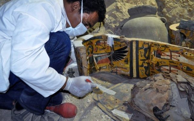 An archaeologist works on a wooden coffin discovered in a 3,500-year-old tomb in the Draa Abul Nagaa necropolis, near the southern Egyptian city of Luxor, on April 18, 2017. (AFP PHOTO / STRINGER)