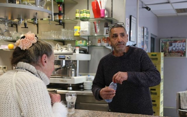 French bar owner Amar Salhi serves a customer at his bar in Sevran, northeast of Paris, April 13, 2017. (AFP/Adam PLOWRIGHT)
