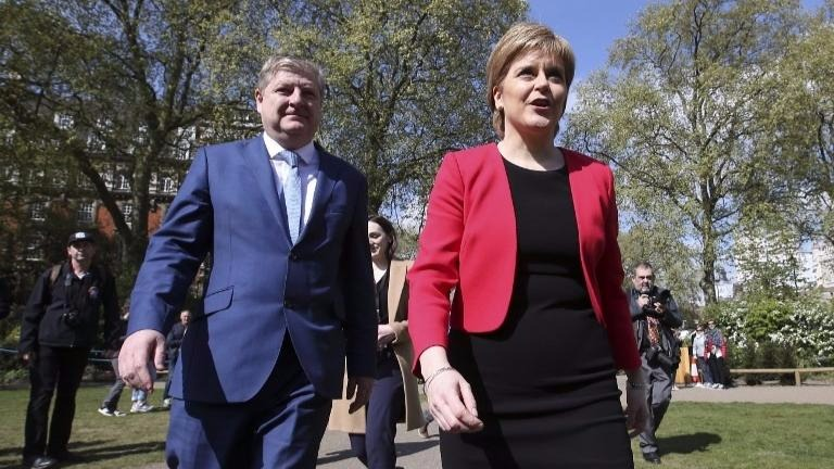 Scotland's First Minister and Scottish National Party leader Nicola Sturgeon (R) walks with deputy leader and member of parliament Angus Robertson (L) during a media facility outside the Houses of Parliament in central London on April 19, 2017. (Daniel LEAL-OLIVAS / AFP)