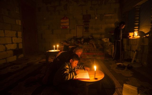 A Palestinian woman helps her son study by candlelight, at their makeshift home in the Khan Yunis refugee camp in the southern Gaza Strip, April 19, 2017. (AFP/Mahmud Hams)