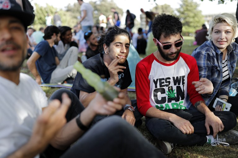 Israelis smoke marijuana joints in Jerusalem on April 20, 2017 during a rally at the Rose garden, to celebrate 420 and to express their defiance of current laws. (AFP PHOTO / THOMAS COEX)