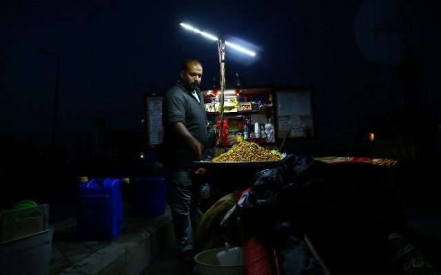 A Palestinian street vendor waits for customers during a power cut in Gaza City, on April 20, 2017. (AFP Photo/Mohammed Abed)