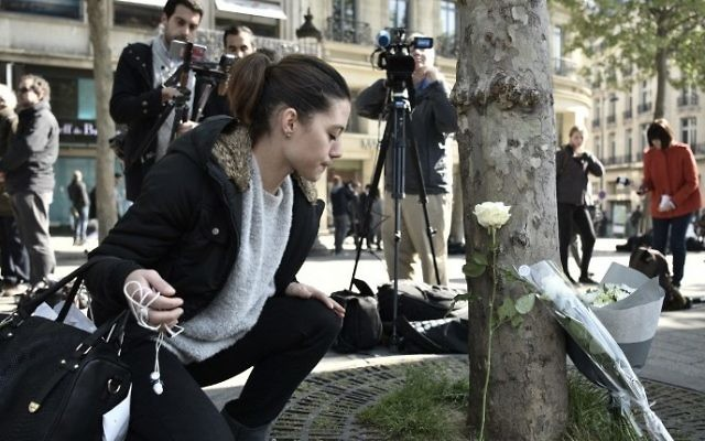 A woman places a flower at the spot where a shooting occured on the Champs-Elysees avenue in Paris, on April 21, 2017 a day after a gunman opened fire on police on the avenue, killing a policeman and wounding two others in an attack claimed by the Islamic State group. (Pilippe Lopez/AFP)